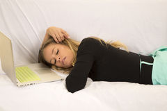Woman in green skirt layign with laptop sleeping Stock Photography