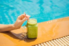 Woman with a green smoothies of spinach and banana on the background of the pool. Healthy food, healthy smoothies.  stock image