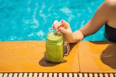Woman with a green smoothies of spinach and banana on the background of the pool. Healthy food, healthy smoothies.  royalty free stock images