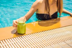 Woman with a green smoothies of spinach and banana on the background of the pool. Healthy food, healthy smoothies.  stock images