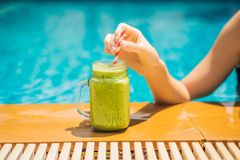 Woman with a green smoothies of spinach and banana on the background of the pool. Healthy food, healthy smoothies.  royalty free stock photography