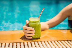 Woman with a green smoothies of spinach and banana on the background of the pool. Healthy food, healthy smoothies.  royalty free stock photo