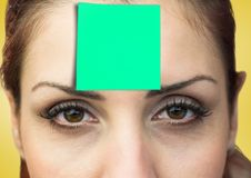 Woman with green sticky note on her forehead Stock Photo
