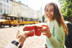 Attractive happy smiling woman sitting in the center of old city with paper cup of coffee Royalty Free Stock Photos