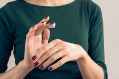 Woman in a green T-shirt and a maroon manicure applying hand cream Royalty Free Stock Photo