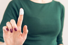 Woman in a green T-shirt and a maroon manicure shows hand cream Royalty Free Stock Image