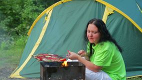 A woman in a green T-shirt is sitting in the forest on the background of a tent, the fire is blowing in her brazier. The stock footage