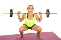 Woman green tank top fitness squat front look up Stock Photography
