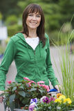 Woman in green top shopping in garden centre, pushing trolley full of flowers, smiling, portrait Royalty Free Stock Photos