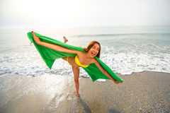 Woman in green towel on the beach Stock Image