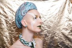 Woman with a green turban on her head. Beautiful bald woman with a green turban on her head. Beauty queen, close up portrait model. Massive jewellery made of Stock Photos