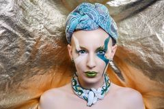 Woman with a green turban on her head. Beautiful bald woman with a green turban on her head. Beauty queen, close up portrait model. Massive jewellery made of Stock Photo