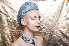 Woman with a green turban on her head. Beautiful bald woman with a green turban on her head. Beauty queen, close up portrait model. Massive jewellery made of Stock Photography