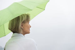 Woman With Green Umbrella Against Clear Sky Royalty Free Stock Image