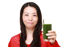 Woman with green vegetable juice. Studio shot of young Japanese woman on white background Royalty Free Stock Photo