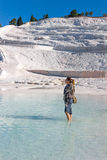 Woman in green water. A woman enjoys thermal waters against the white mountain made of salt Royalty Free Stock Photos