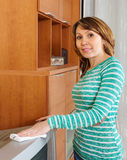 Woman in green wiping the dust on TV Stock Images