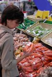 Woman at the greengrocery. Woman shopping in a supermarket in the vegetables area Stock Photo