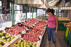 Woman in greengrocery. A woman looking at fruit in a greengrocery shop Royalty Free Stock Images