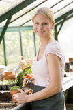 Woman in greenhouse raking soil in pot smiling Stock Photos