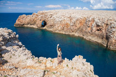 Woman greeting on cliff above sea Minorca coast Stock Photos