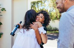 Woman greeting couple for having a new house. Smiling young women with wine bottle congratulating her friend. Housewarming party with friends stock photo