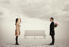 Woman greeting man with flowers Royalty Free Stock Photography