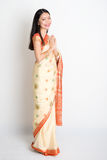 Woman with greeting pose. Full length mixed race Indian Chinese girl with sari dress in greeting gesture, standing on plain background Royalty Free Stock Photography