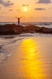Woman greets sun the sea shore Stock Image
