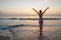 Woman greets sun the sea shore Royalty Free Stock Photo