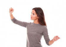 Woman in grey blouse pointing to her right Royalty Free Stock Images