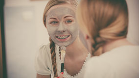 Woman with grey clay mud mask on her face. Skincare. Blonde woman in bathroom with gray clay mud mask on her face. Young lady taking care of skin. Spa beauty Royalty Free Stock Photography