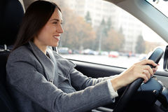 Woman in grey coat driving a car Royalty Free Stock Photos