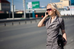 Woman in grey dress walking and calling by phone Stock Image