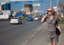 Woman in grey dress walking and calling by phone. Outdoors Royalty Free Stock Photography