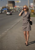 Woman in grey dress walking and calling by phone Stock Photos