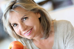 Woman with grey hair eating red apple Royalty Free Stock Photo