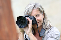 Woman with grey hair using modern camera Royalty Free Stock Image