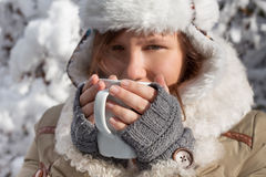 Woman in grey mittens, coat and hat with white fur drinking from Stock Photo