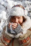 Woman in grey mittens, coat and hat with white fur drinking from Royalty Free Stock Photography