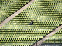 Woman in Grey Shirt Sitting on Stadium Chair Royalty Free Stock Photo