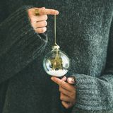 Woman in grey sweater holding decorative glass ball, square crop. Woman in grey warm woolen sweater holding toy glass decorative ball in hands, copy space royalty free stock photography