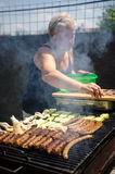 Woman grilling sausages and meat Royalty Free Stock Images