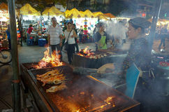 Woman grills shrimps at night market. In Puh Quoc, Vietnam, Jan 20, 2014 Royalty Free Stock Photo