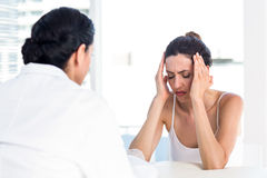 Woman grimacing in front of her doctor Stock Photo
