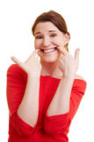 Woman grimacing with her fingers Stock Images