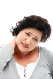 Woman grimacing in pain as she rubs her neck Stock Photos
