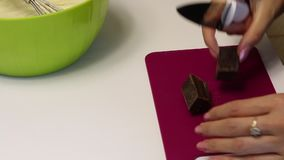 A woman is grinding black chocolate. With a knife, on a cutting board. To make a dessert.  stock video footage