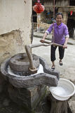 A woman grinds soybeans to produce milk Royalty Free Stock Image