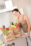Woman with groceries in the kitchen Stock Photography